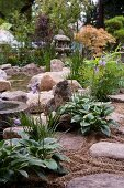 Large stones and plants on edge of garden pond with Japanese lamp and Japanese maple in background