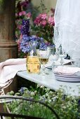 Rustic French wine decanter, glasses, plates and table linen on garden table