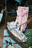 Pristine gardening gloves with feminine French patterns in old wire basket on garden chair