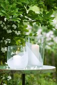 Two large candle lanterns on round metal table in garden