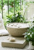 Simple fountain made of porous concrete with shells and pebbles next to potted plants with white flowers