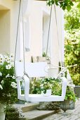 DIY tree swing made from white wooden chair and two ropes