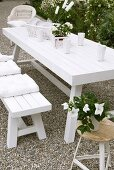 White garden table and matching bench decorated with flowers and set with porcelain crockery