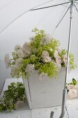 Bouquet of floribunda roses, scabious and lady's mantle beneath umbrella