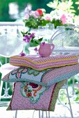 Small jug of bougainvillea flowers and patchwork cushions with complex floral motifs on white metal chair