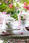 Kaffeetasse mit Rose unter Käseglocke auf einem Gartentisch