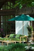 Comfortable terrace sofa with green cushions below parasol in front of rustic farmhouse