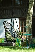 Net swing chair hanging from tree in front of rustic farm house