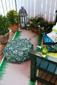 Small seating area on balcony with floor cushions and runner next to green wooden bench