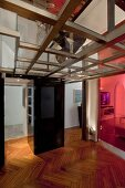 Glass and steel ceiling above foyer with transparent coloured glass partition