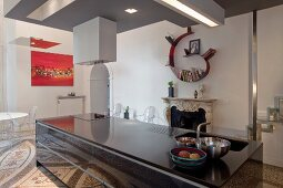 Monolithic, black kitchen island in front of open fireplace in open-plan interior with terrazzo floor