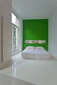 Modern bed with white bedspread against green wall on white epoxy resin floor