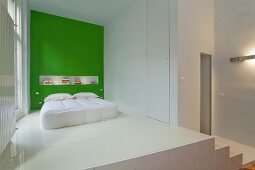 Bedroom area on platform with white epoxy resin floor and bed against green wall