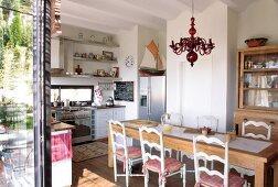 Natural wood furniture in simple kitchen-dining room with Mediterranean ambiance provided by turned wooden chairs and red glass chandelier