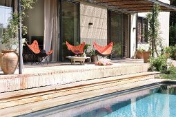 Seating area with butterfly chairs on Mediterranean terrace with pergola roof; detail of pool in foreground