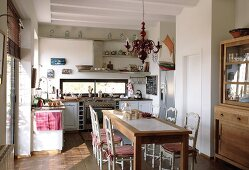 Sunny kitchen-dining room in Mediterranean country house style with turned wooden chairs at modern wooden table