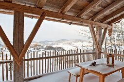Wooden furniture and snow on roofed terrace in mountain landscape