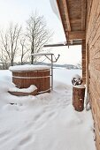 Well next to wooden house in winter landscape