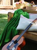Wooden bench with blanket, cushions and guitar
