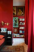 Red bedroom - open doorway next to red curtain and view of floating shelves of books on red wall