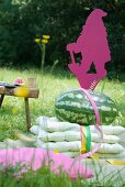 Cushions, water melon and brightly coloured garden gnome shaped from sheet metal