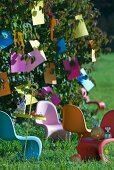 Brightly coloured plastic chairs below tree with paper decorations