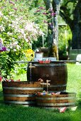 Paper boats as garden party decorations on miniature ponds in wooden barrels