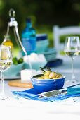 Small blue dish of Greek olives, wine glasses and sheep's cheese on set table