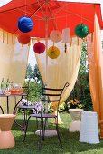 Bistro table with metal chairs and colourful paper lanterns below market umbrella draped with voile curtains