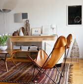 Bat chair on ethnic rug in front of sideboard with drawers
