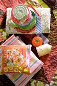 Colourful hotchpotch of haberdashers' goods spread on patchwork blanket