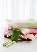Soft toy and stack of patchwork blankets