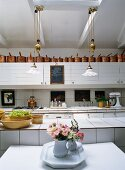 Large, white-tiled kitchen with free-standing island and Art-Nouveau pendant lamps