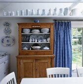 Crockery in rustic dresser next to terrace door with gingham curtain