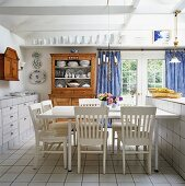 Dining room in mix of styles - white-painted wooden chairs at dining table and wooden dresser on white tiled floor