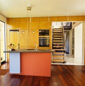Kitchen counter with colourful front panel in open-plan kitchen with view of staircase through wide doorway
