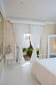 Romantic bedroom in Mediterranean villa - white, airy curtains at open terrace doors