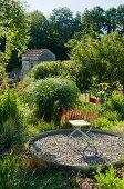 Klappstuhl auf Kiesboden in kreisförmigem Ausschnitt in mediterranem Garten