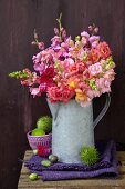 Late summer still-life with large bouquet of snapdragons in zinc jug and spiky sweet chestnuts on folded linen cloth