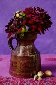 Dark red dahlias in classic ceramic jug against purple background; acorns on embroidered linen cloth