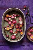 Pink and red everlasting flowers floating in old zinc dish on purple linen napkin