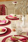 A table laid for a celebration in pink and wine red, with modern place mats, glass holders hand-crafted from metal and a romantic candle holder