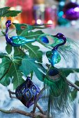 Stylised glass peacocks with real tail feathers and Oriental Christmas bauble on fig tree