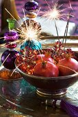Dish of pomegranates and burning sparklers with coloured glass candlesticks in background