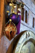Exotic Christmas arrangement of copper-coloured pendant and purple bauble and tassel hanging on wrought iron door handle