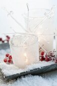 Dish holding lit tea lights in glasses decorated with artificial snow and red holly berries
