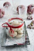 Jar of aniseed biscuits on tray in artificial snow