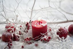 Red candle and holly berries in artificial snow