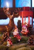 Metal stag ornament, candlestick and gnome Christmas tree baubles in imitation landscape