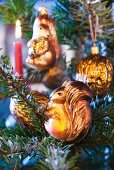 Animal-shaped baubles hanging on Christmas tree